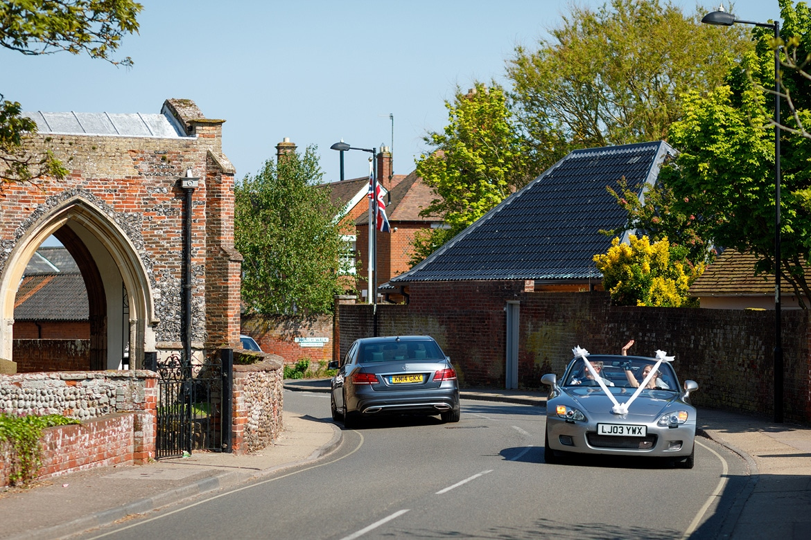 the bride arrives at aldeburgh church in her dads sportscar