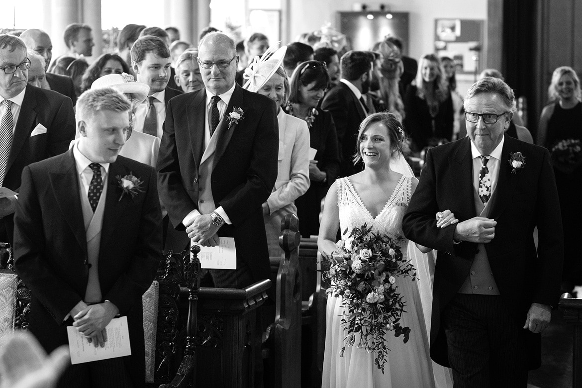 bride and her father walk down the aisle of aldeburgh church