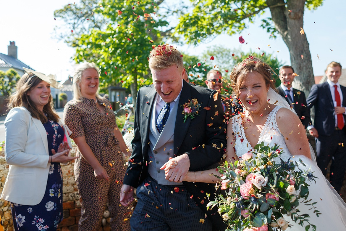 bride and groom run through the confetti outside aldeburgh church