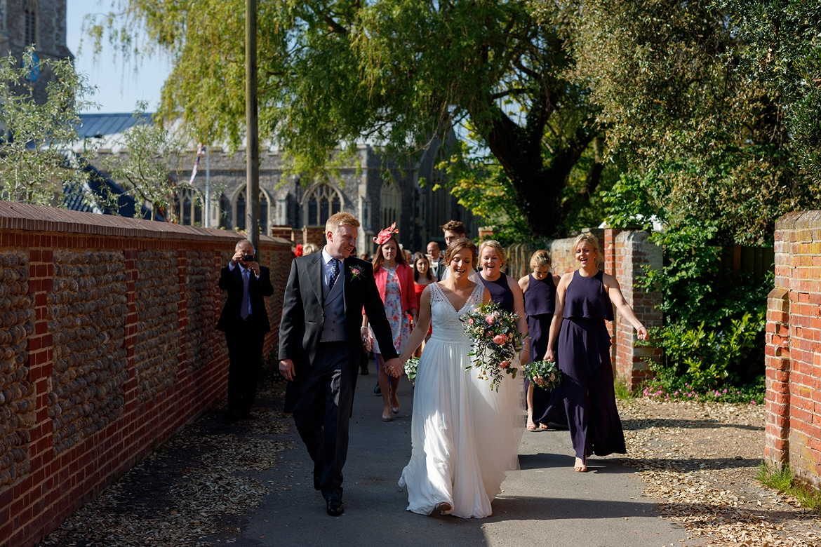 the wedding party walks through aldeburgh