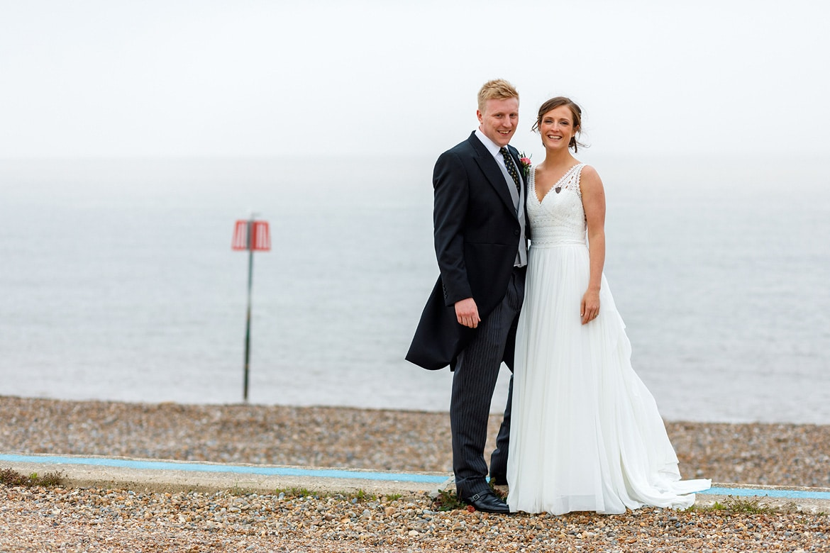 bride and groom pose in front of aldeburgh sea front