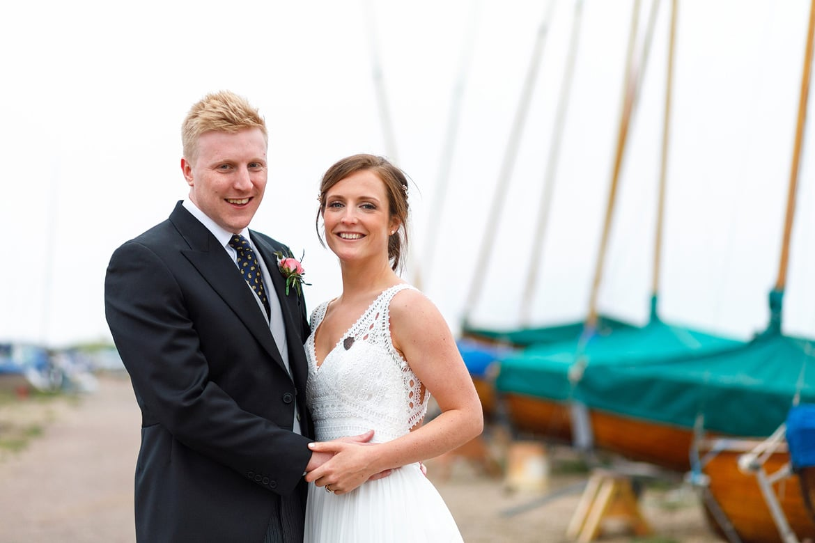bride and groom pose with yachts in the background