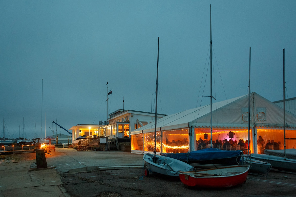 aldeburgh yacht club as night falls on the wedding marquee