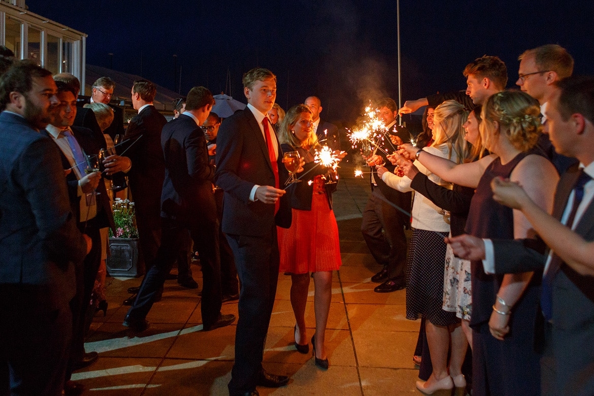 guests light sparklers outside aldeburgh yacht club