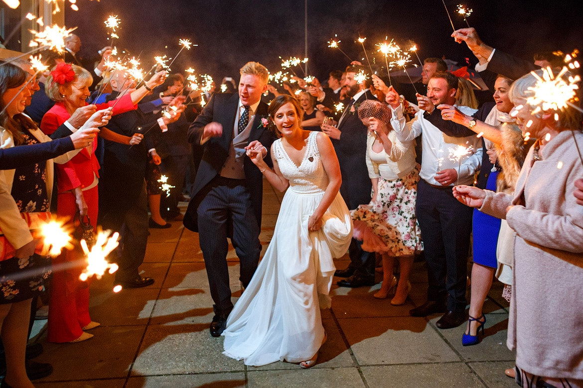bride and groom run through the sparklers at their aldeburgh yacht club wedding