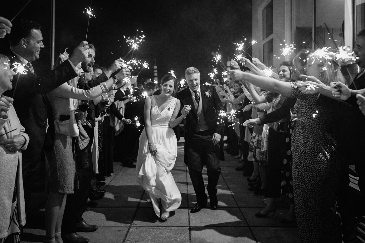 bride and groom run through the sparklers