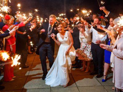 bride and groom run through sparklers at their aldeburgh yacht club wedding