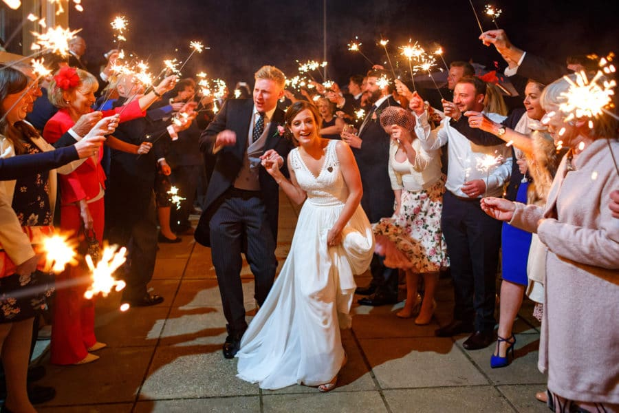 bride and groom run through sparklers at their aldeburgh yacht club wedding