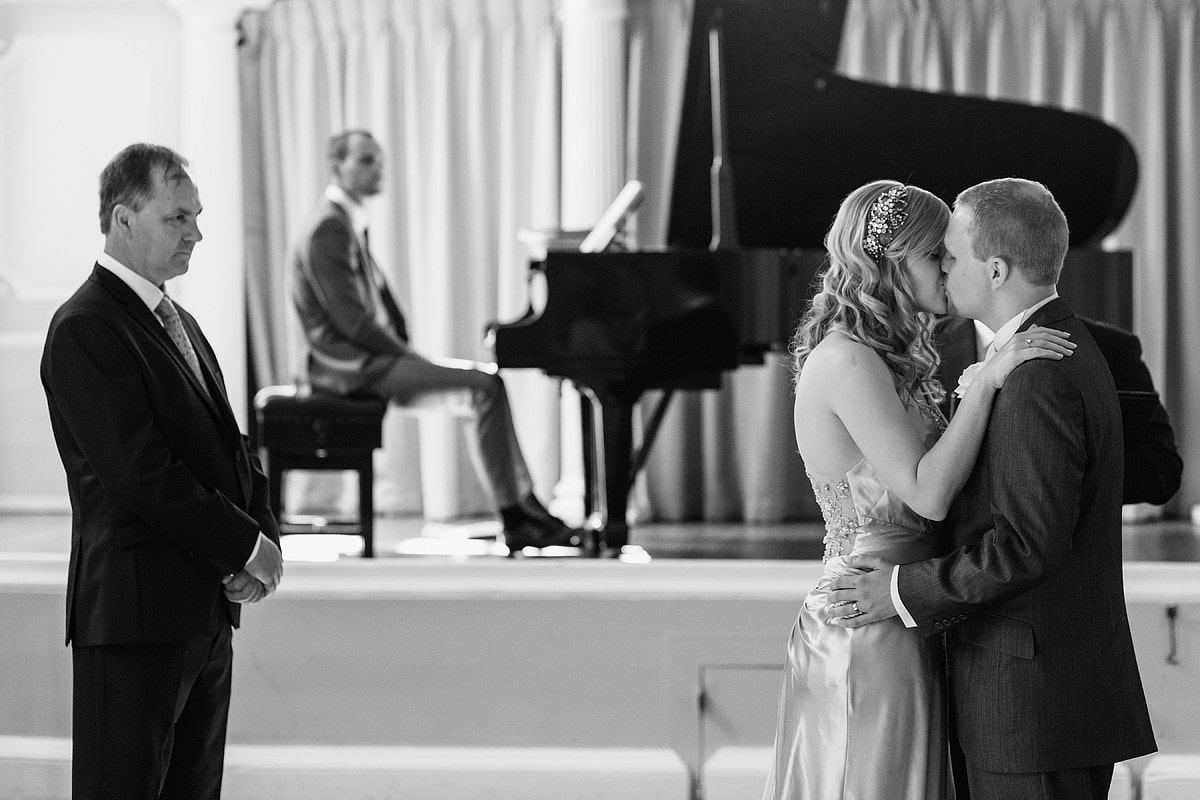 the couple kiss at the end of their assembly house wedding