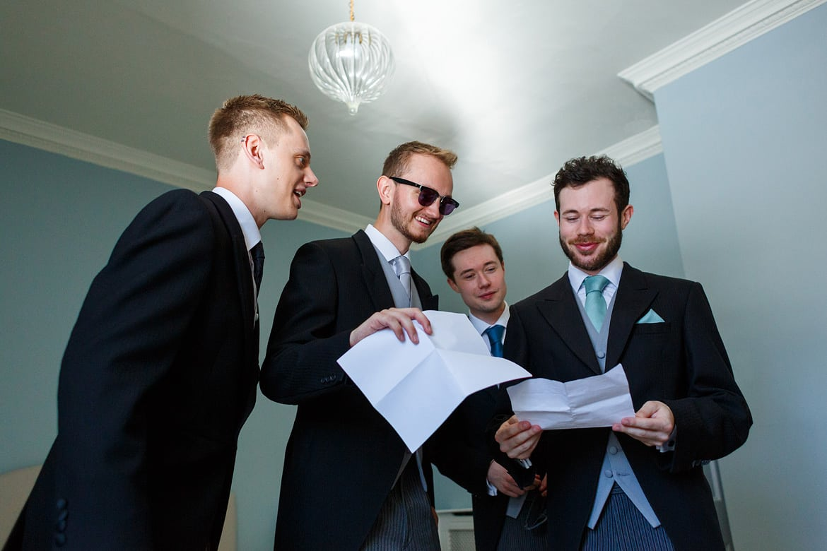 groomsmen look through their duties for the day