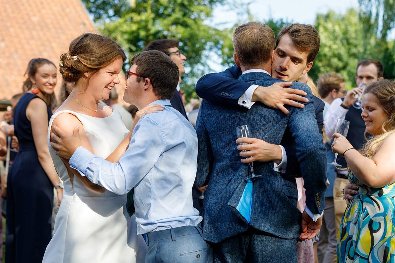 bride and groom hug their guests at their norfolk wedding