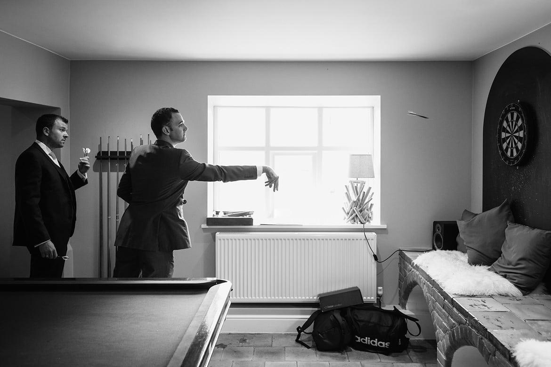 the groomsmen play darts before a godwick barn wedding