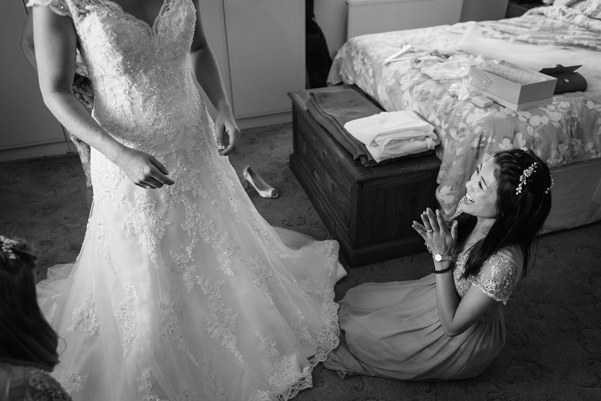 a bridesmaid helps the bride with her dress