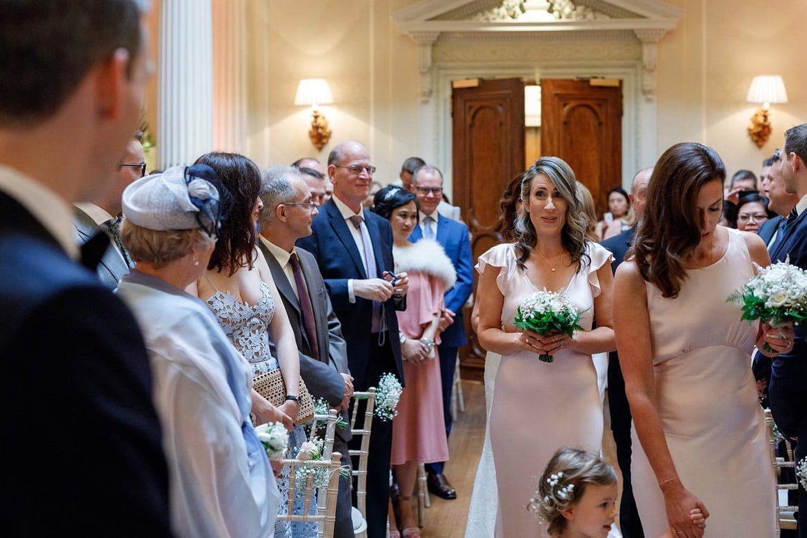 the bridemaids walk down the aisle at hedsor house