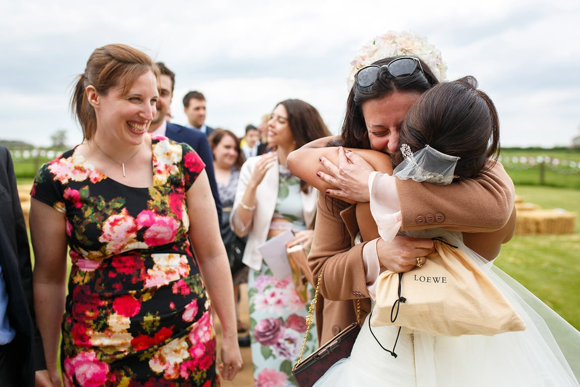 a wedding guest hugging the bride