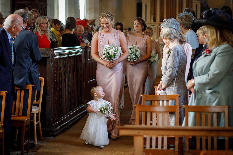 a flower girl walks the aisle at a suffolk wedding