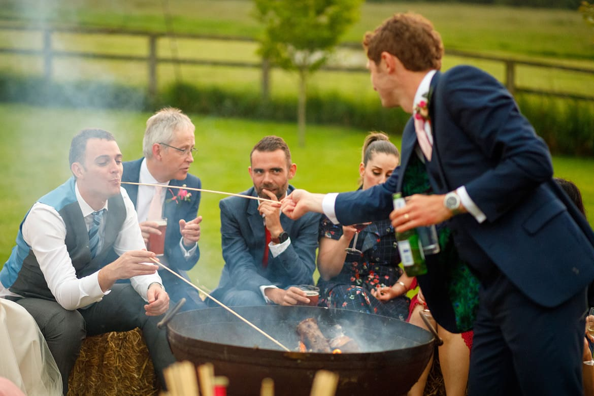 the groom feeds a guest marshmallows at godwick barn
