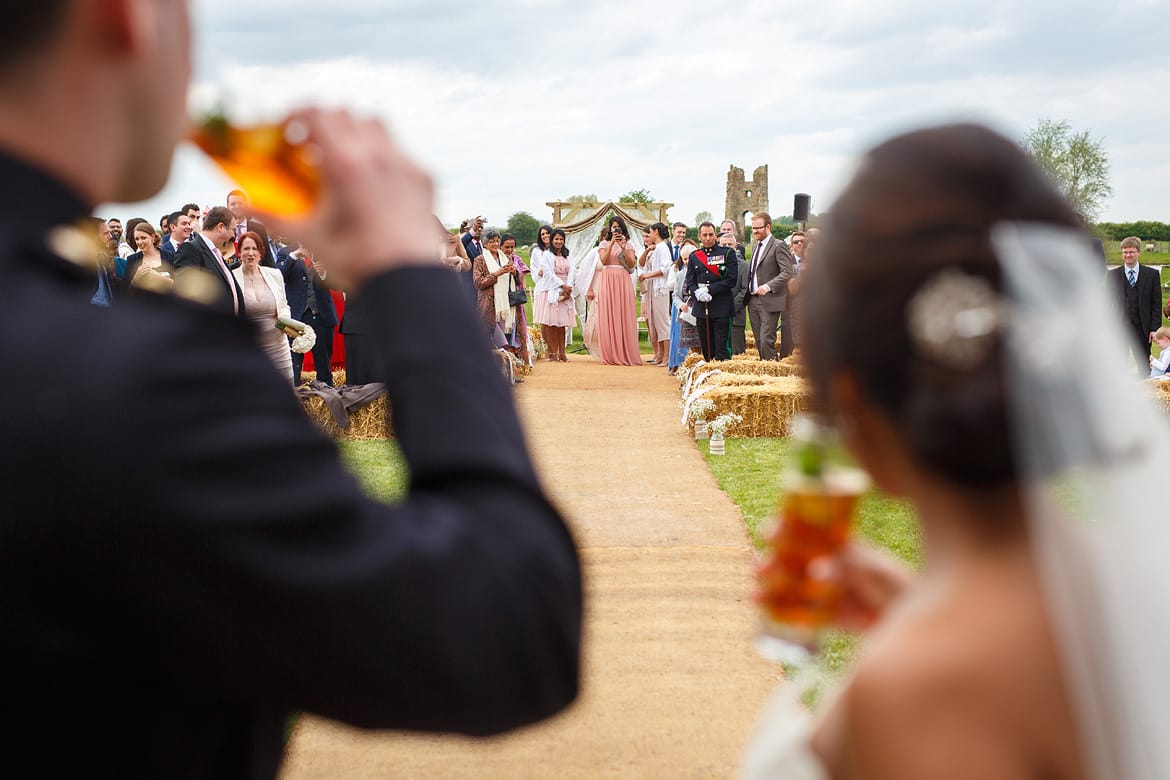 bride and groom look at their wedding guests at godwick hall