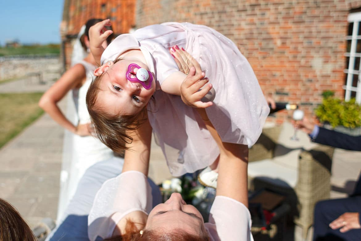 lifting up the flower girl at a cley windmill wedding