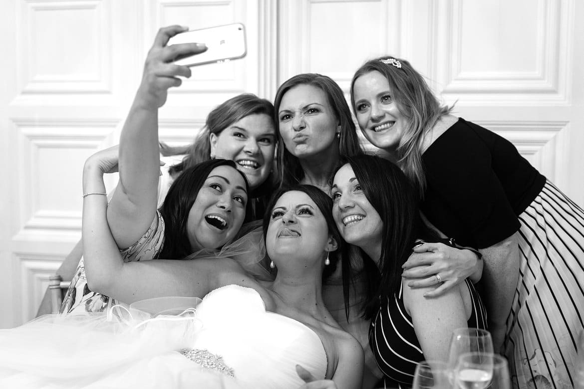 a bride and her guests take a selfie at hengrave hall