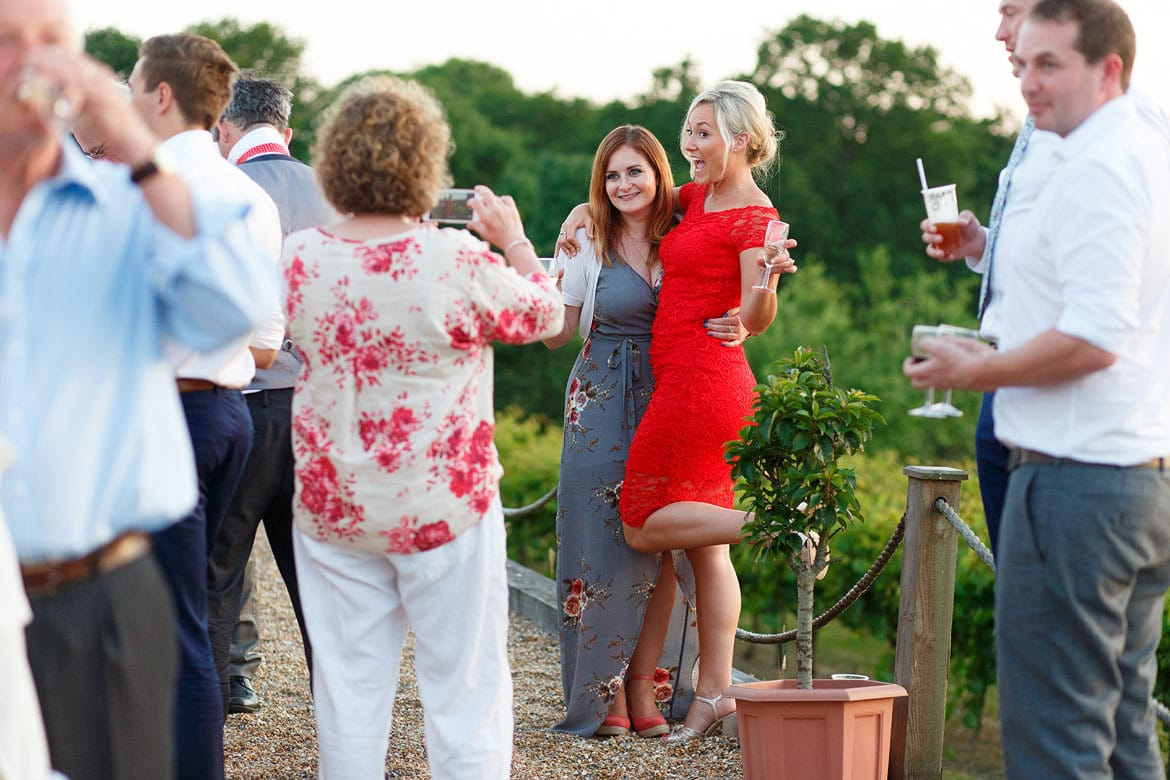 wedding guests pose for photos at bluebell vineyard