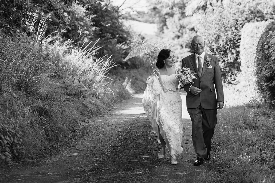 a bride and her father walk to the wedding ceremony at gate street barn