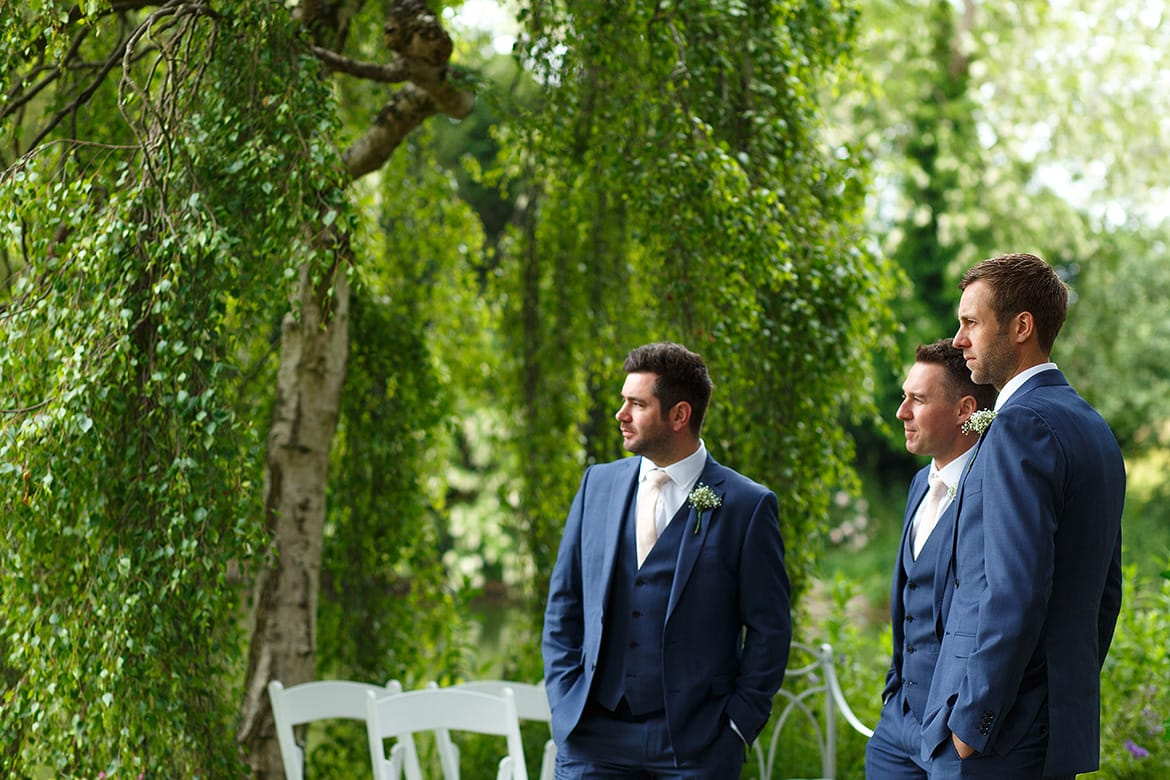 a groom waits for the bride with his groomsmen
