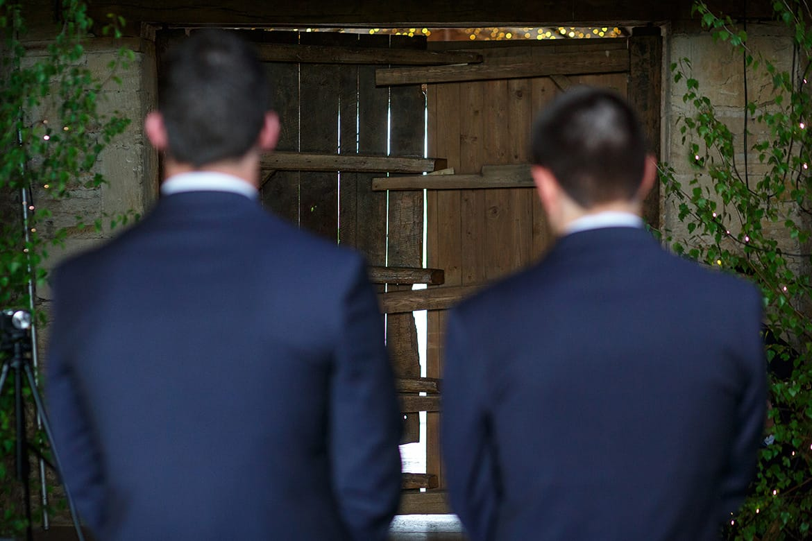 the groom and best man wait for the bride to come through the barn doors