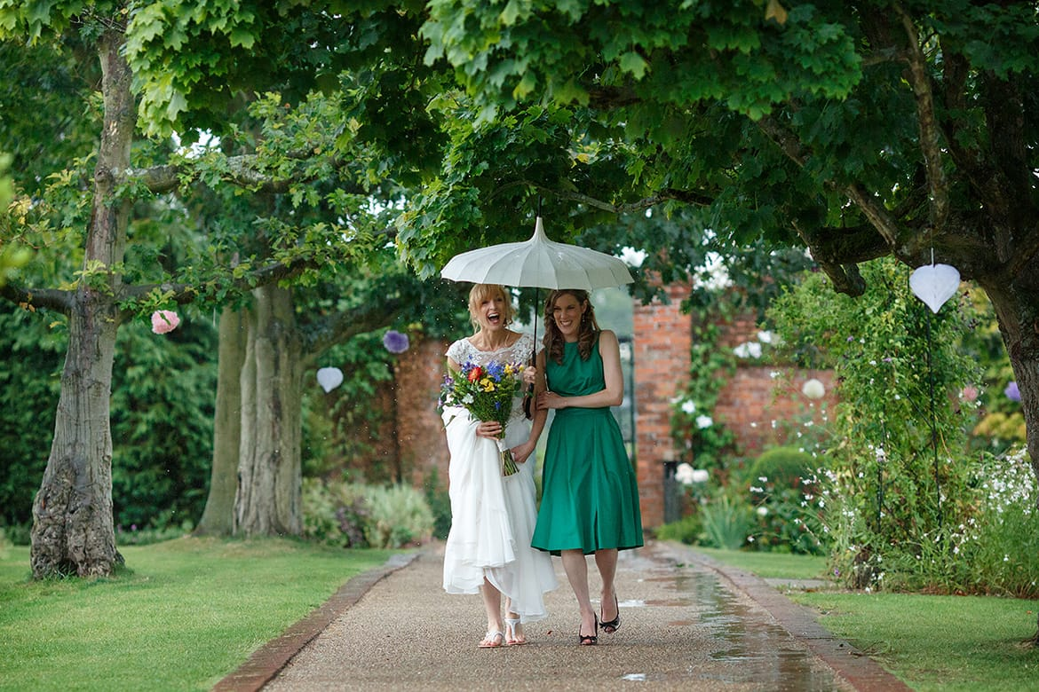 a bride and bridesmaid walk through the rain at gaynes park
