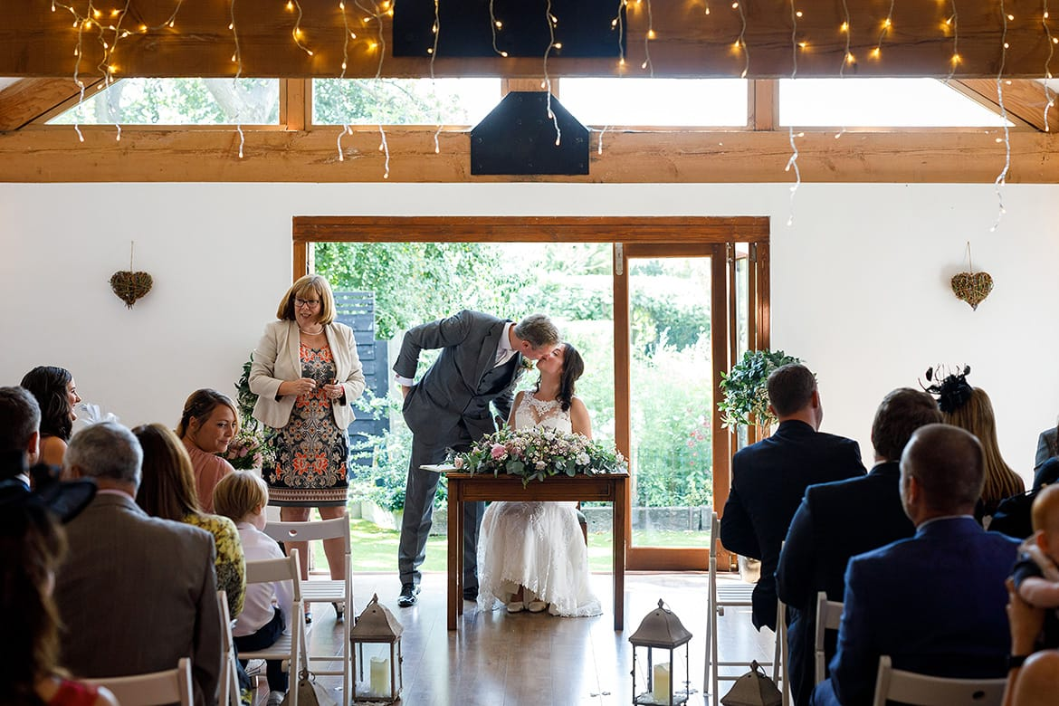 kissing during a maidens barn wedding ceremony