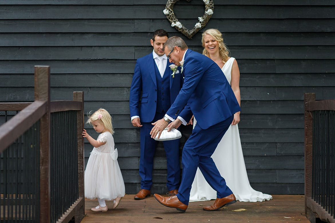 a father chases a flowergirl away from the bride and groom