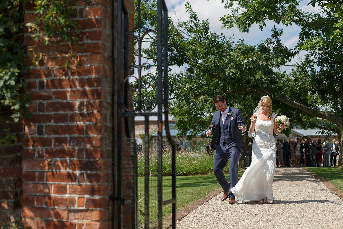 bride and groom walk through gaynes park
