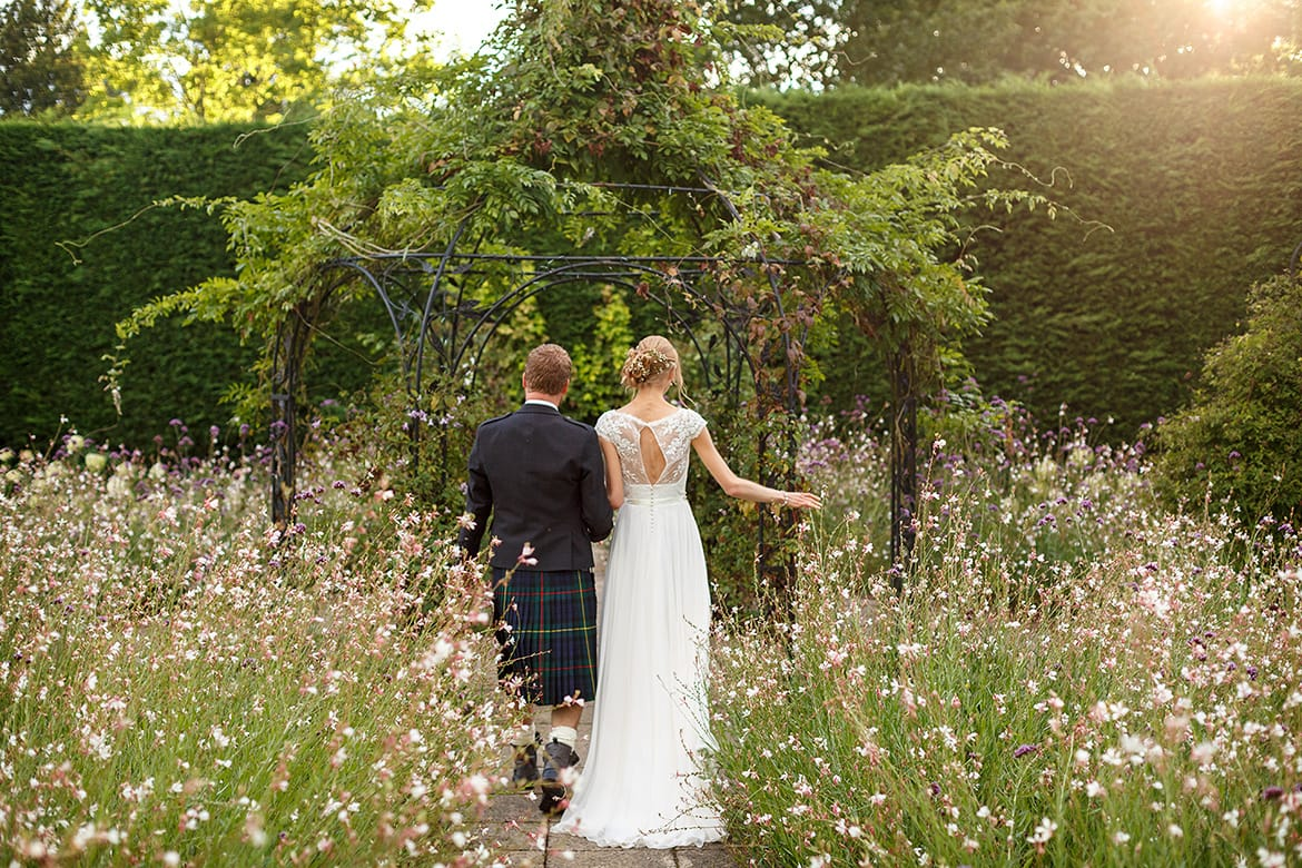 bride and groom walk through the gardens at gaynes park