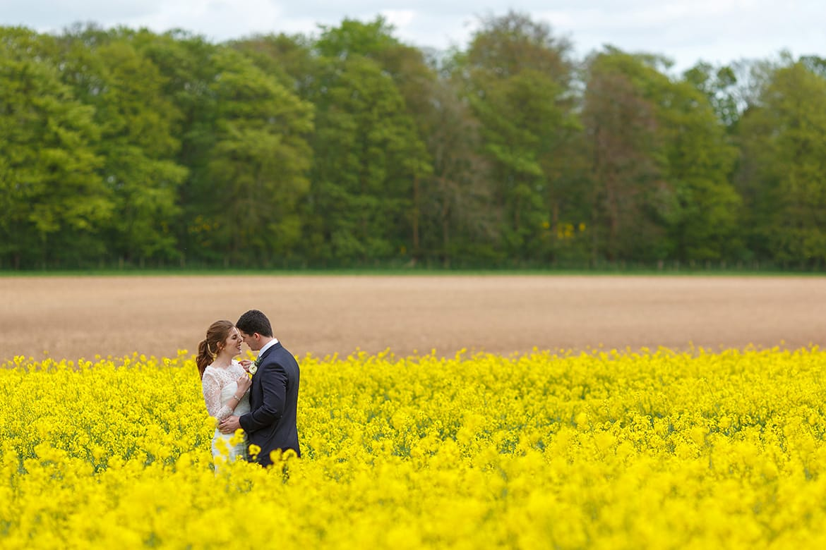bride and groom in the fields at cripps stone barn