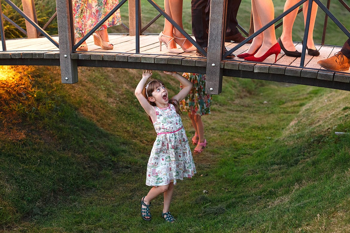 a cheeky girl under the bridge at a barn wedding