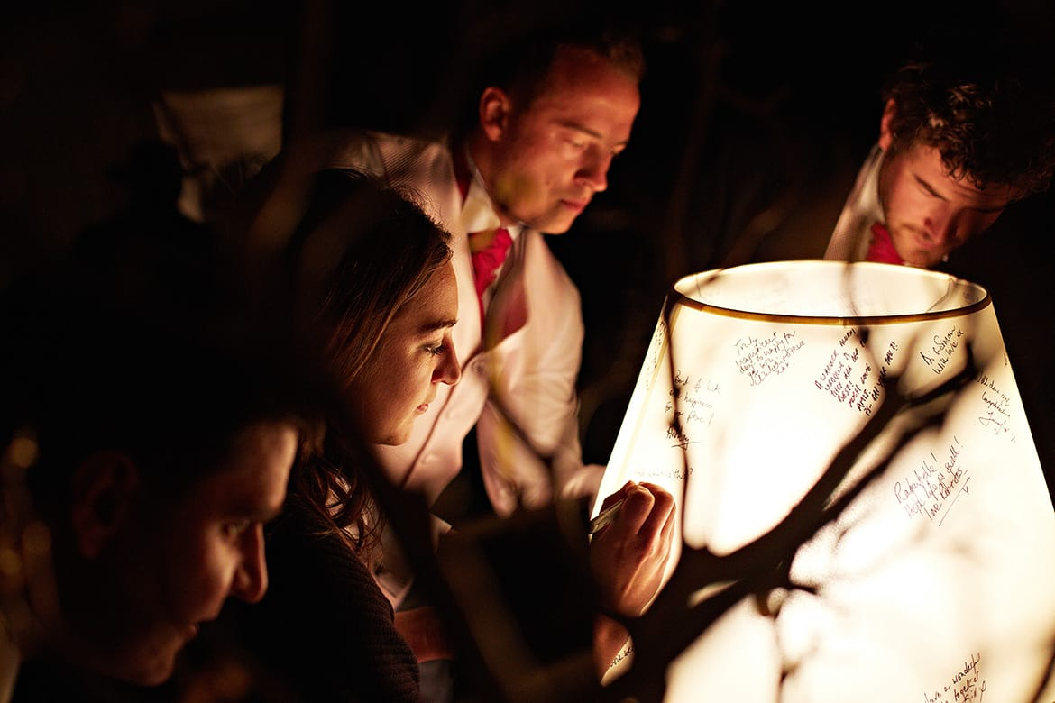 guests sign a lampshade at a barn wedding