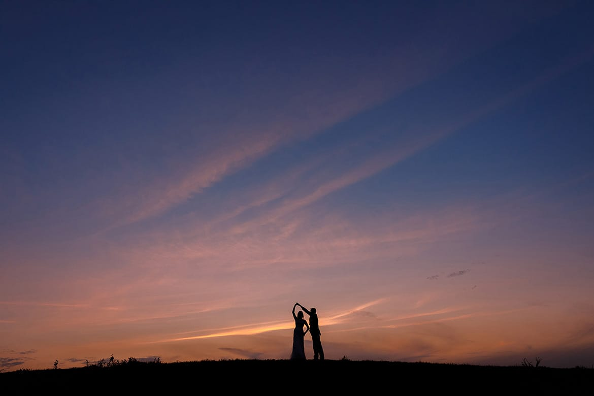bride and groom dance in front of the sunset at a maidens barn wedding
