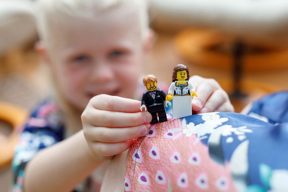 a flowergirl hold a lego bride and groom