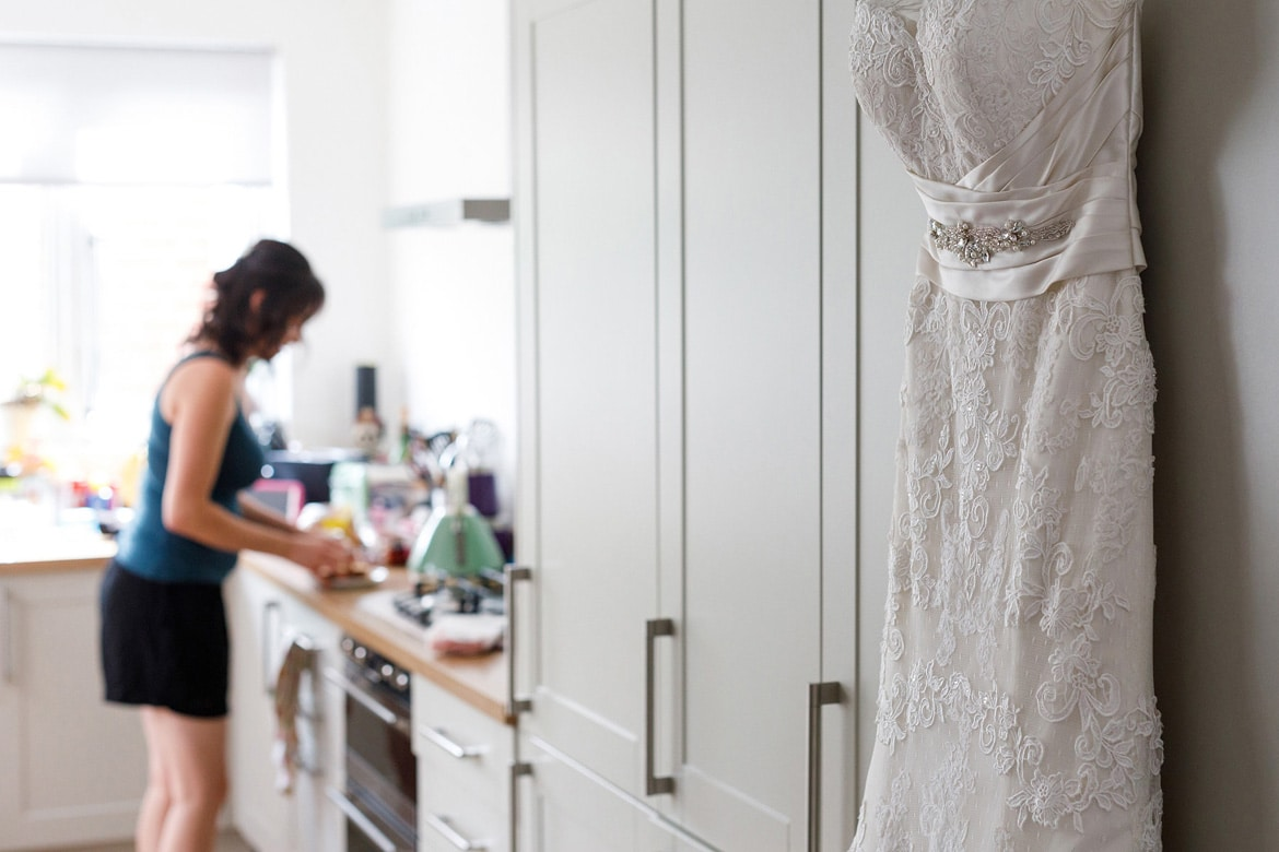 wedding dress hanging in the kitchen with the bride in the background