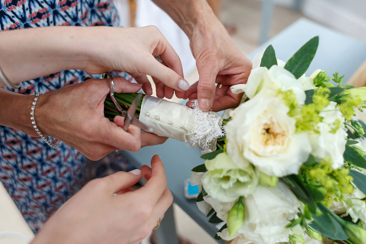 the brides mother helps her with her bouquet