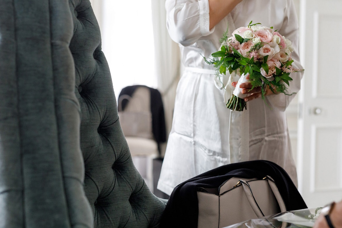 bride holding her bouquet in her dressing gown