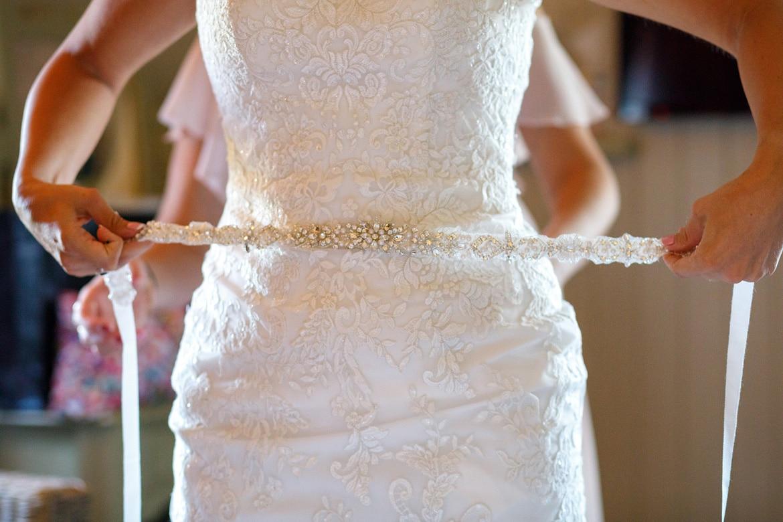 a bride fixes her belt