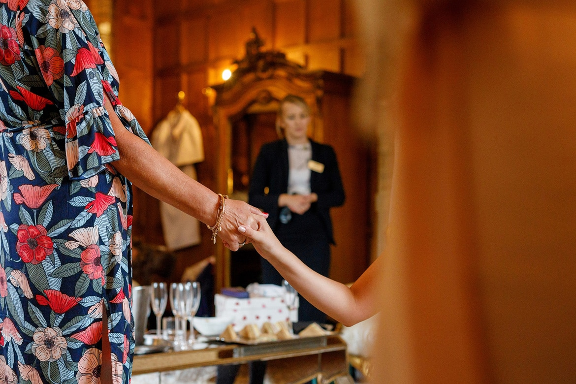 mother and daughter hold hands at a hengrave hall wedding