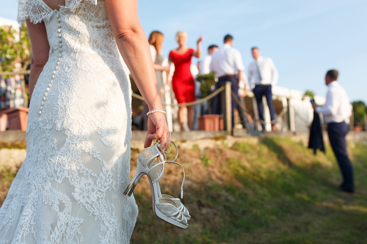 a bride holding her wedding shoes