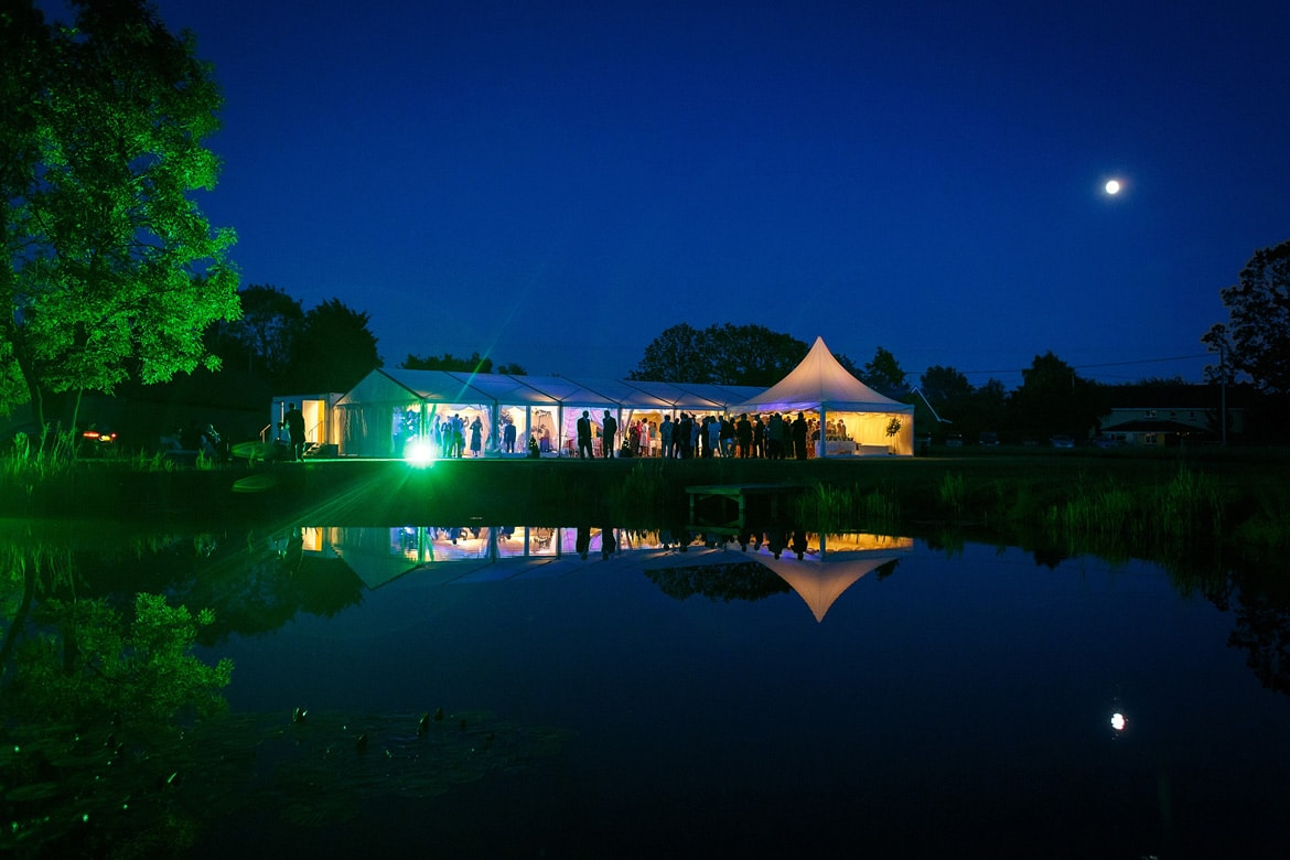 wedding marquee at night reflected in the lake