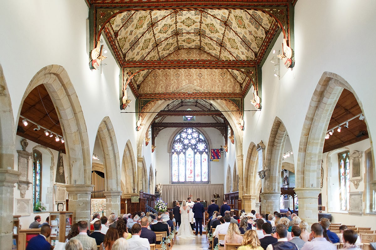 wide shot of a wedding in holy trinity church cuckfield
