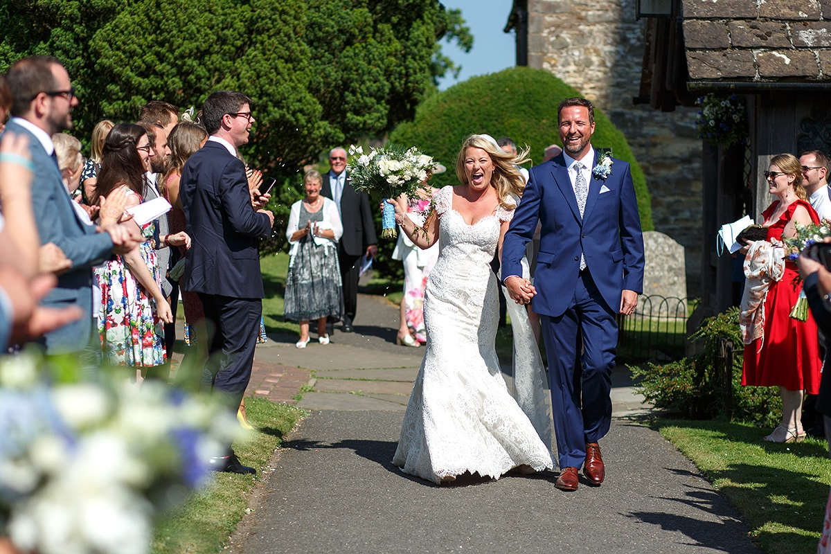 bride and groom walk through the confetti at holy trinity cuckfield