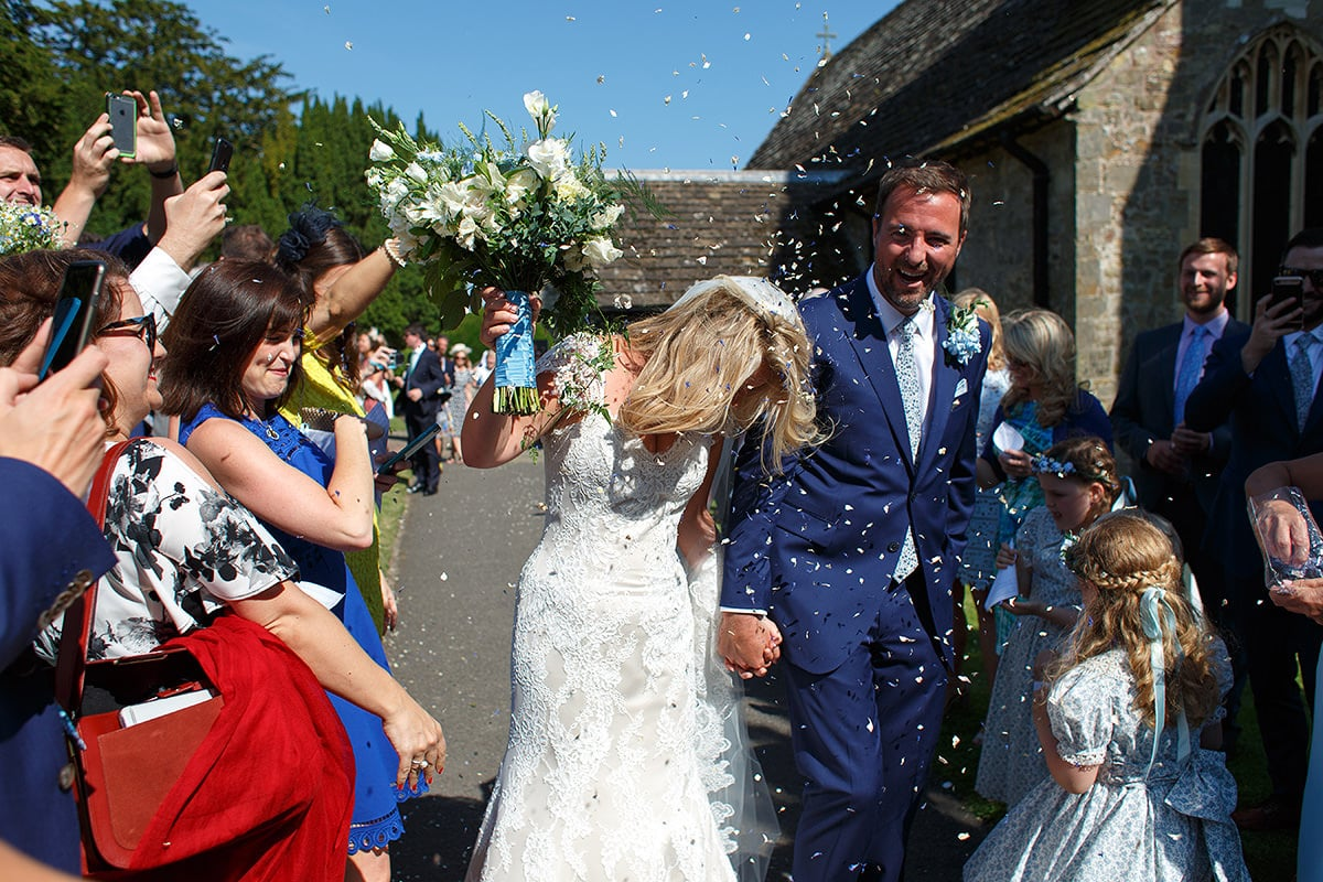 laura and todd walk through the confetti