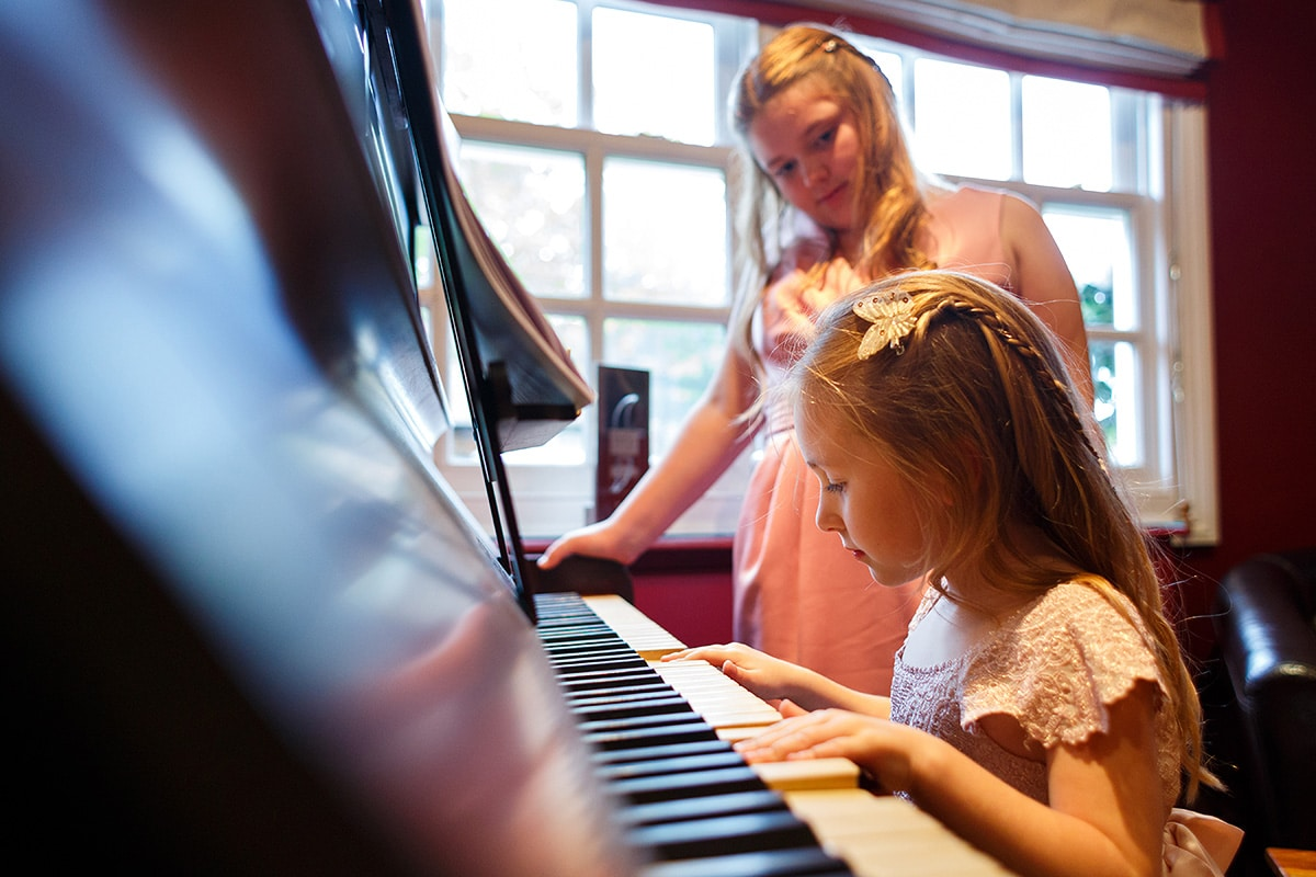 the flower girls play on the piano