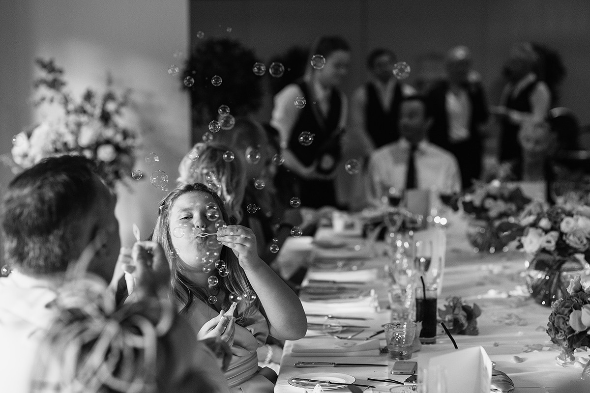 wedding guests blowing bubbles at the dining table